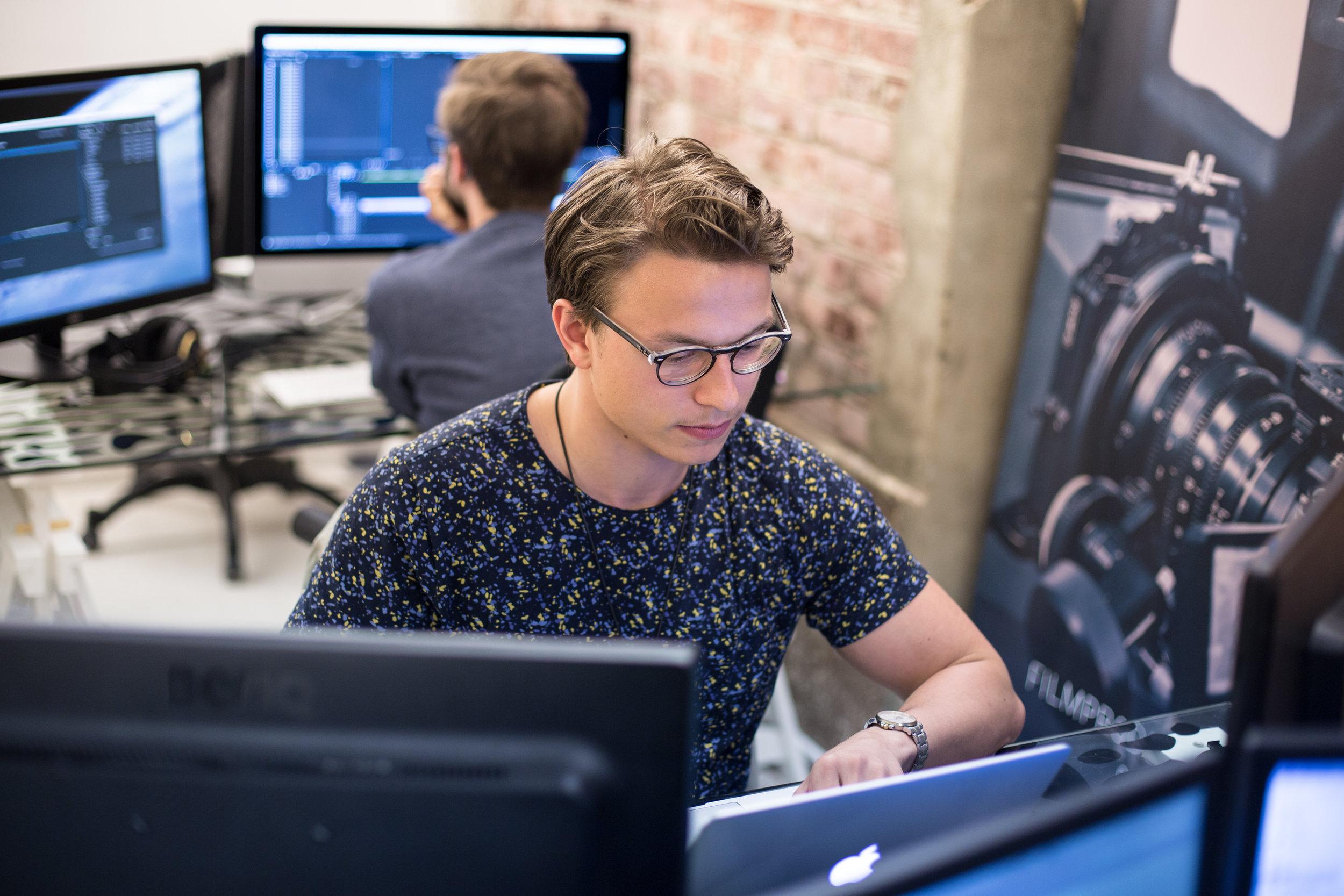 Mann med brunt hår og briller som jobber på en PC på Avia produksjon sitt kontor