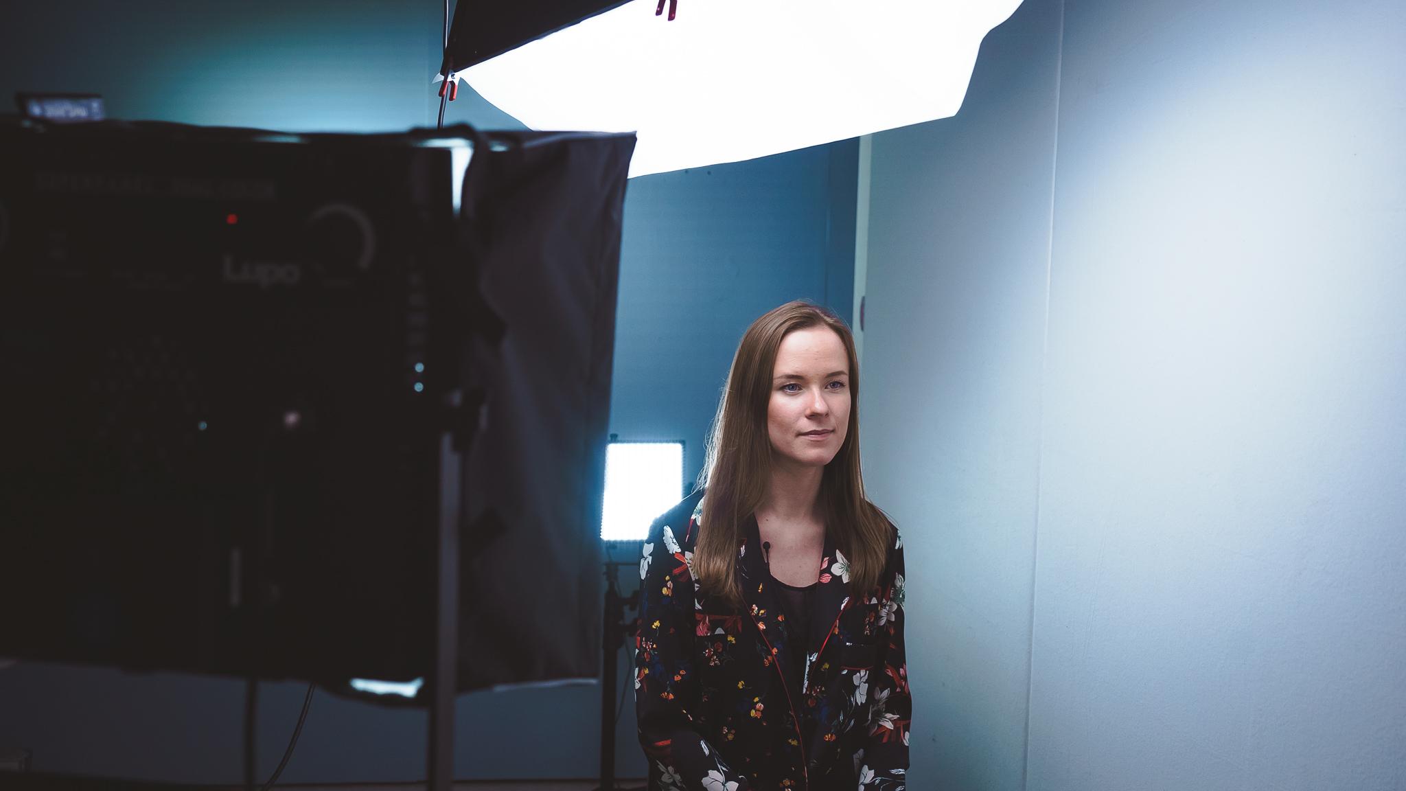 Dame med brunt hår og blomstrete blazer som blir tatt bilde av i Avia produksjon sitt studio