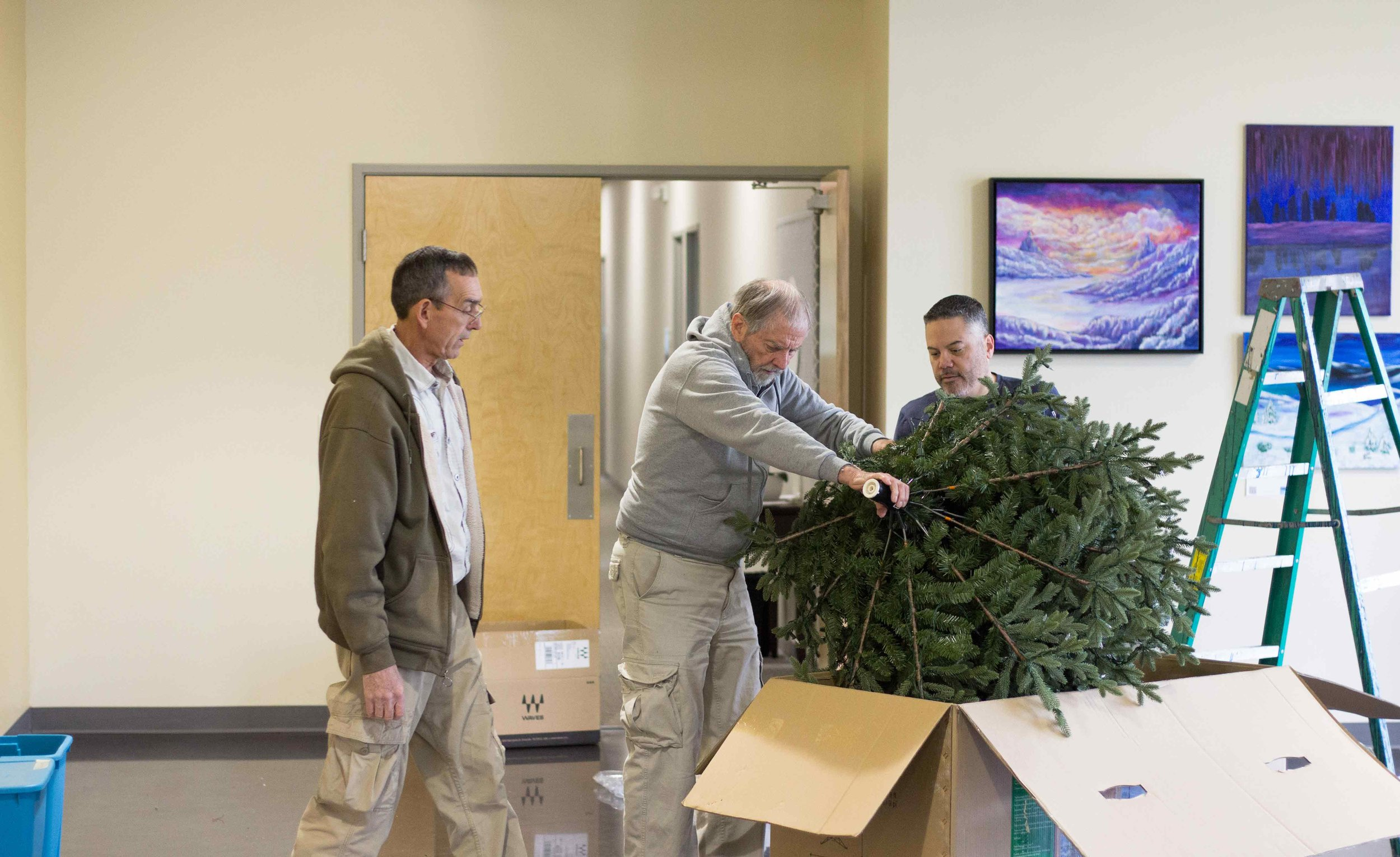Men helping tear down Christmas decorations