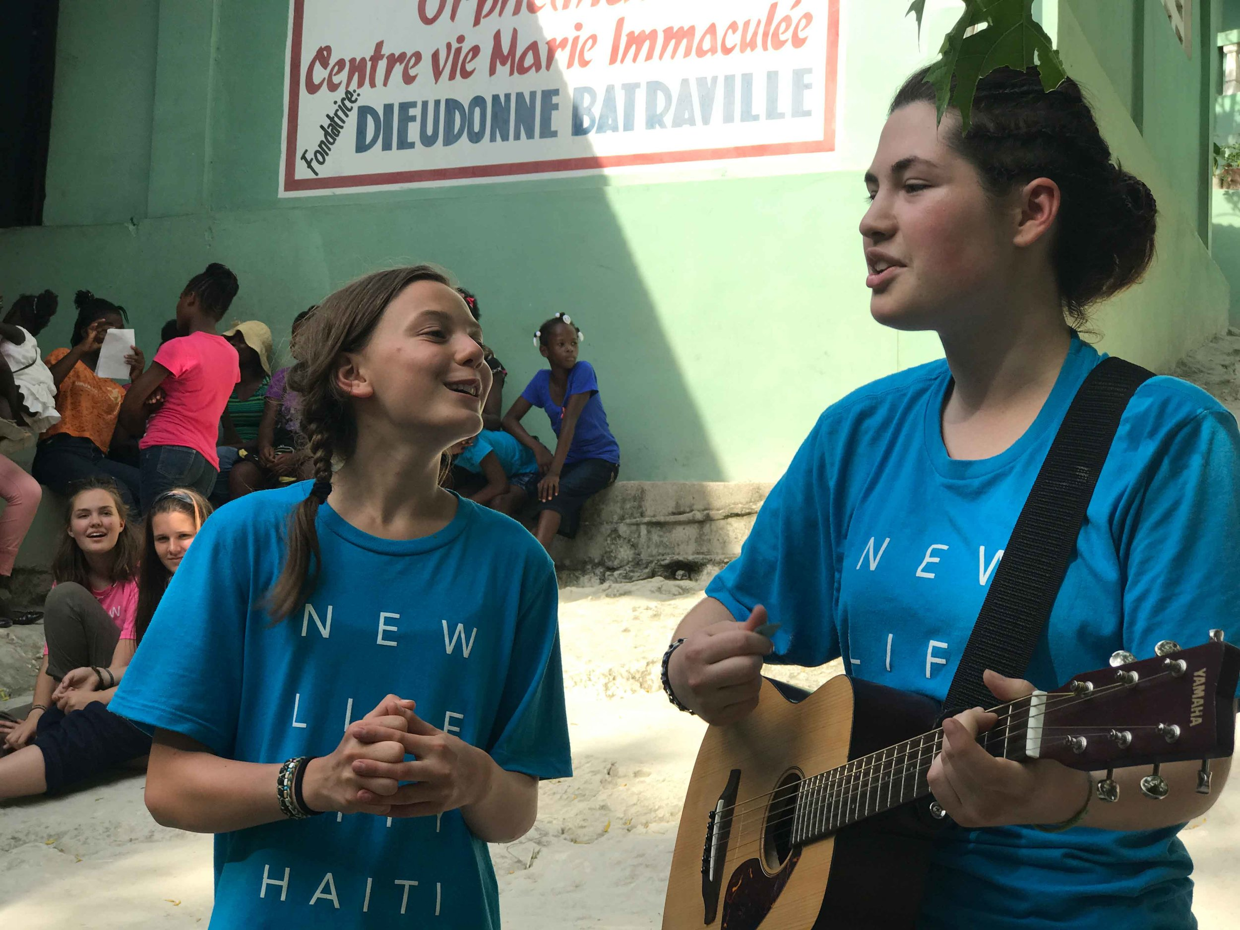 Two City Youth girls on outreach in Haiti singing with a guitar
