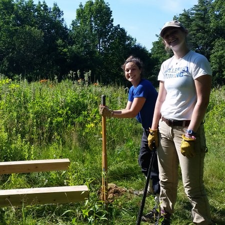 2017 Regional Field Team members, Beanie and Michaela, install interpretive signage at Merrymeeting Fields Preserve.