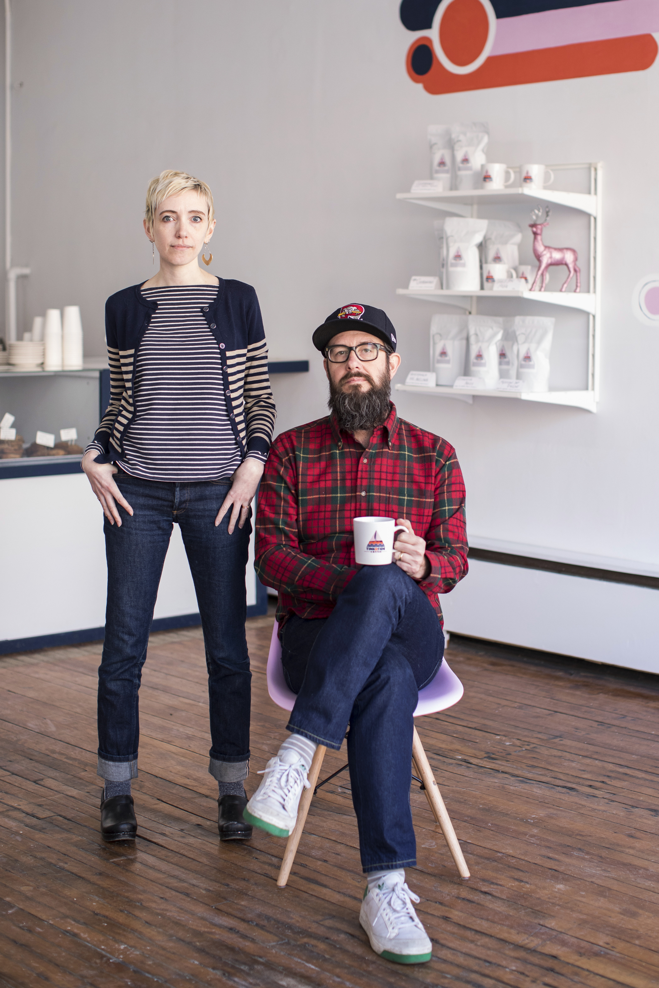 Woman in striped top and jeans stands next to seated man in plaid shirt and ball cap. The man holds a coffee cup. Link opens new window for Alyce Henson Photography Instagram.