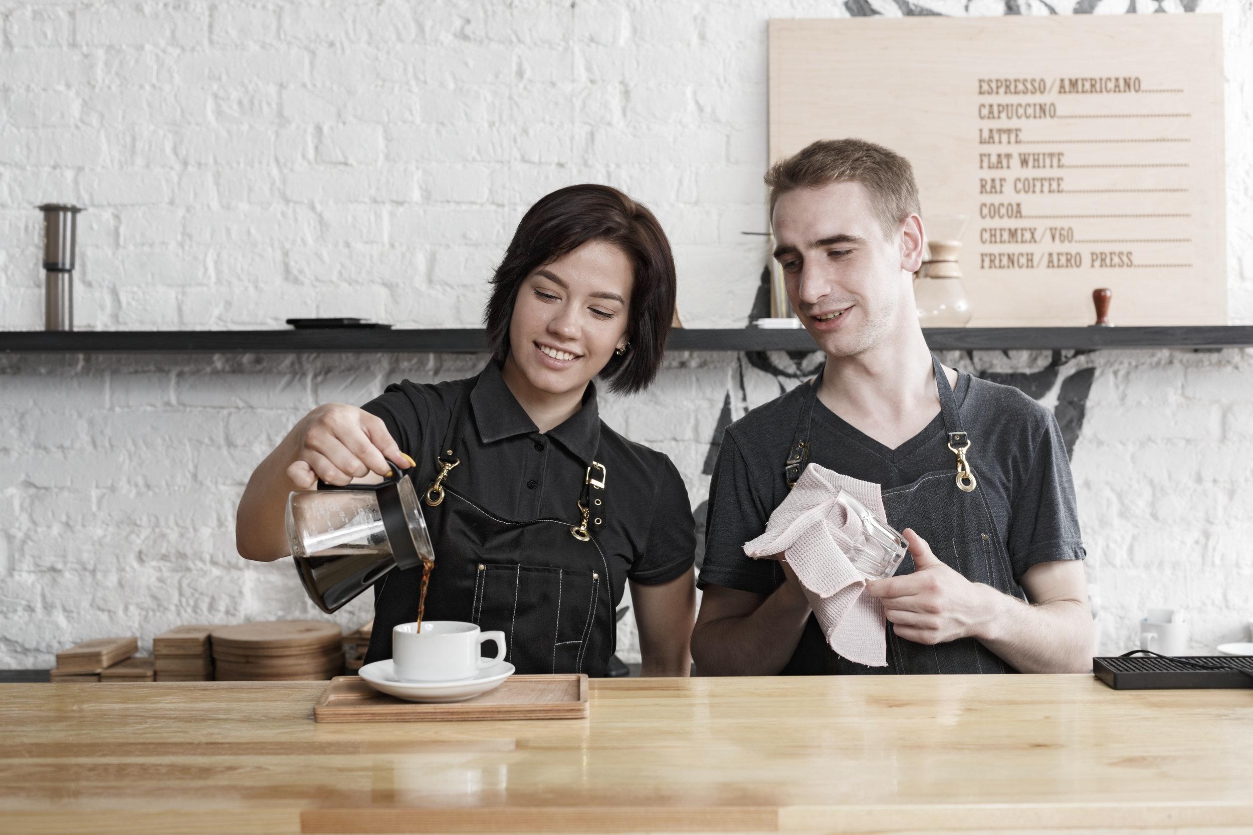 male-and-female-bartenders-brewing-fresh-coffee-PUR5WU3.jpg