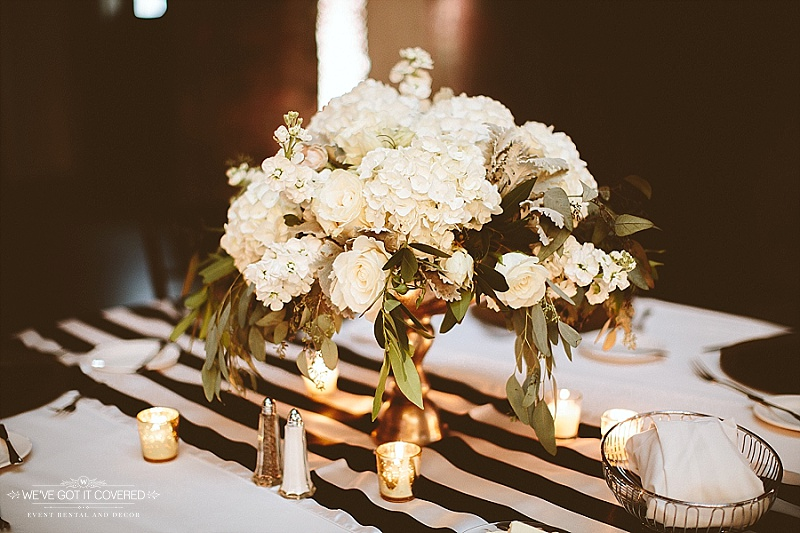 Table decor including flowers, candles and a back and white stripe table runner.