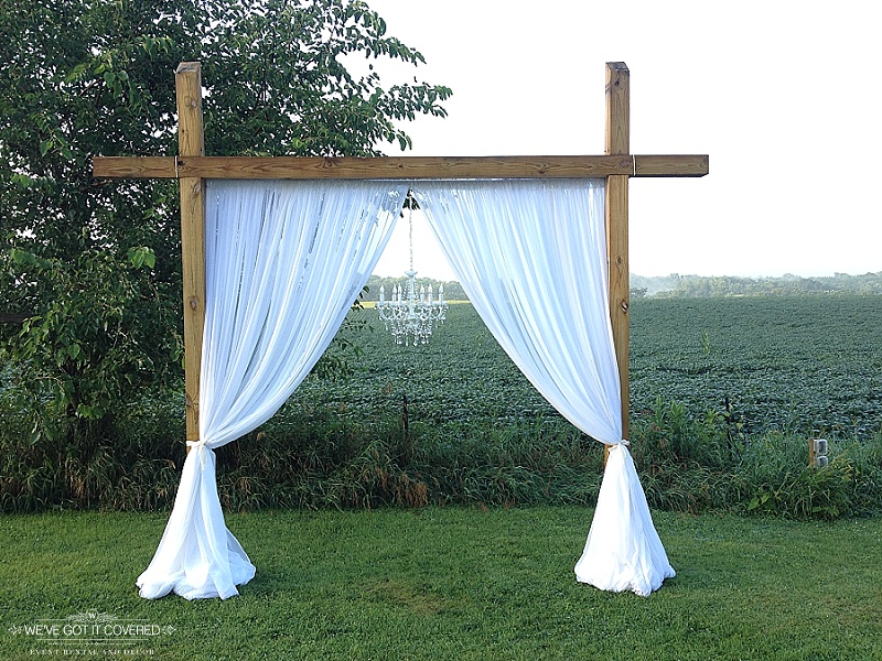 Farm venue arch with white curtain draping and a crystal chandelier hung in the middle of a field