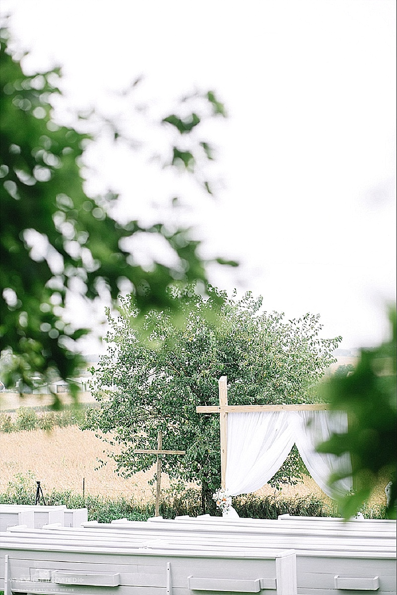 Peek through at the wedding ceremony site with white curtain draping and a beautiful farm backdrop.