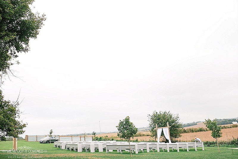 Ceremony site with outdoor pews and trees and draping on the ceremony arch.