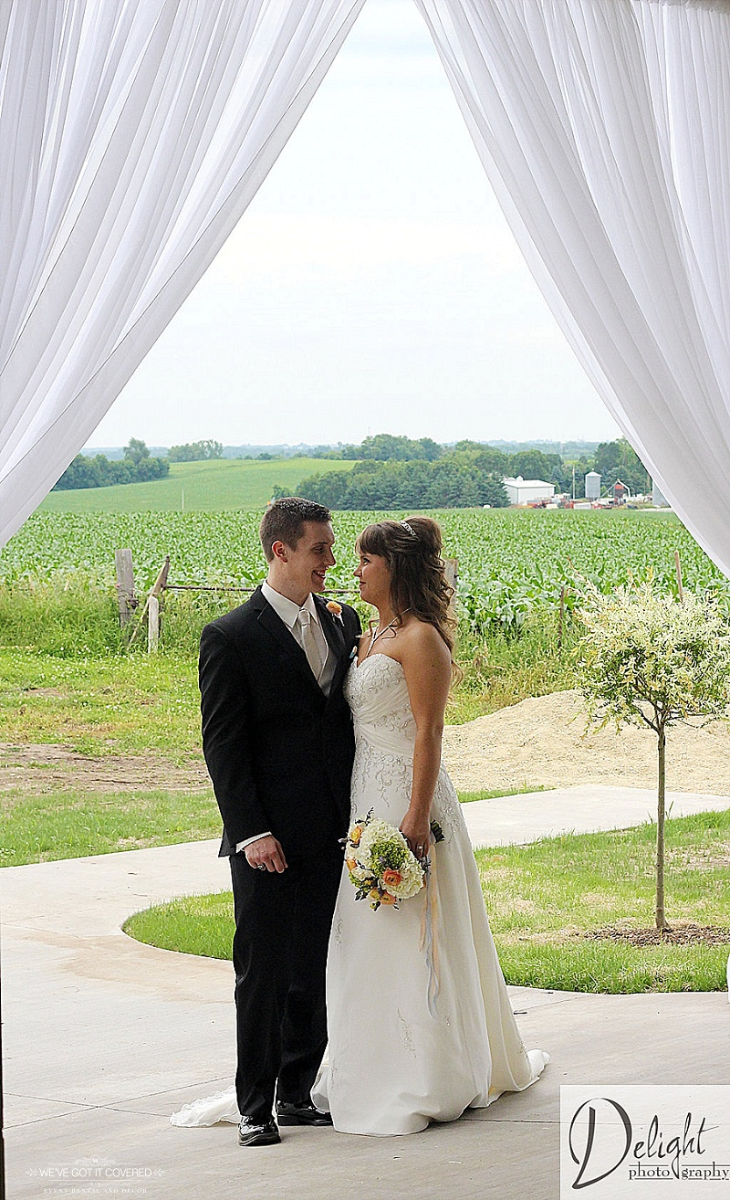Romantic look between newlyweds with draping on an entrance