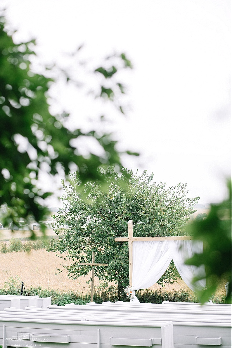 draping on an outdoor farm venue arch with floral tied back
