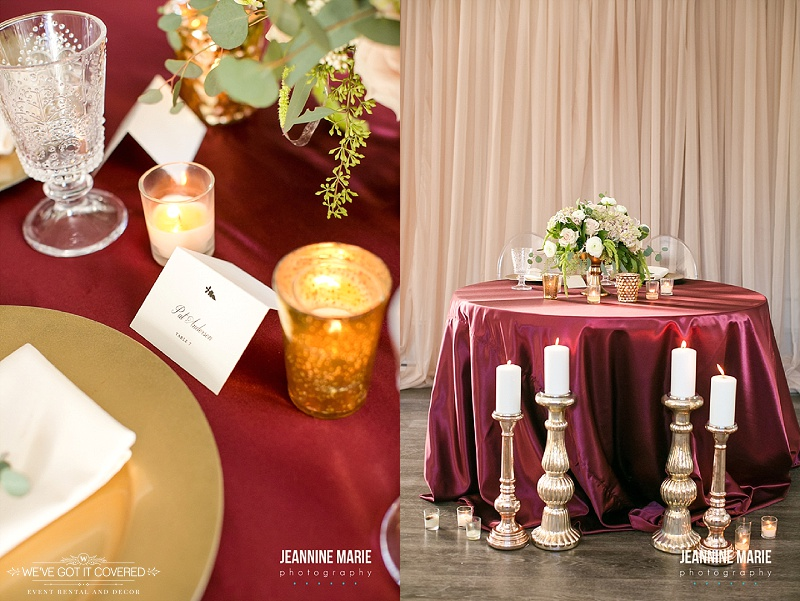 Burgundy linen with tall candlesticks and floral arrangements for centerpiece with a taupe backdrop