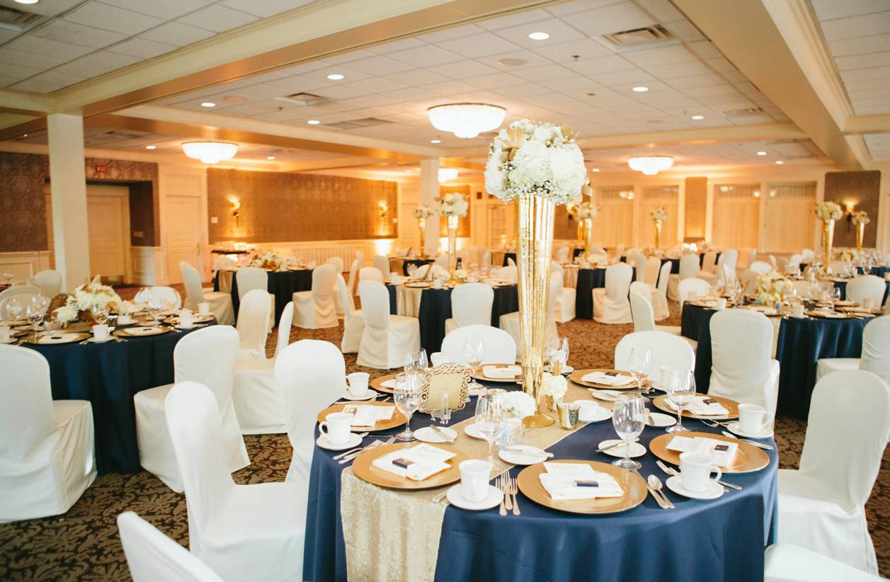 Navy table linens with gold accents of runners, chargers, and tall flower holders