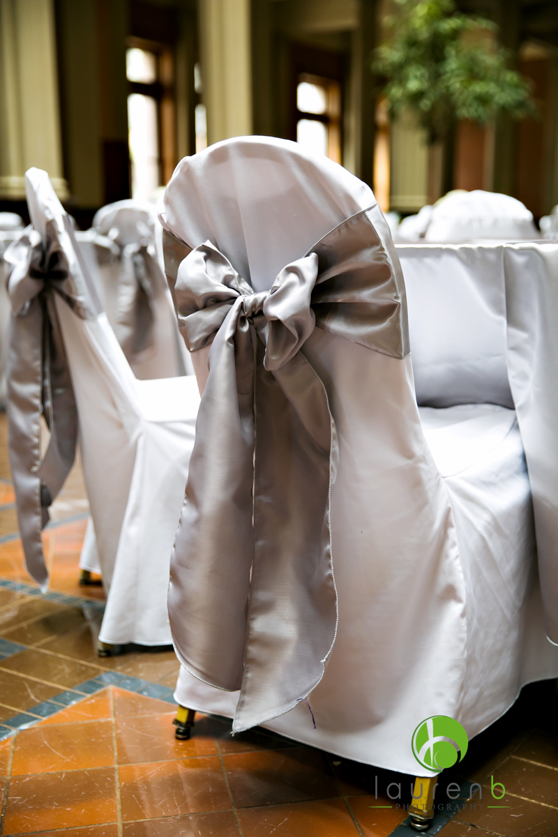 Silver satin sash tied in a bow styled with a white chair cover
