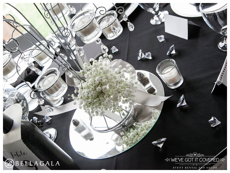 Mirror centerpiece with babys breath, jewels, and crystal votive candle centerpieces