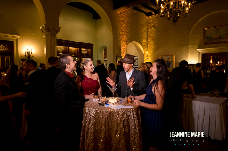 Guests having a good time at a Minnesota wedding reception talking around a cocktail table with a gold rainbow sequin table linen
