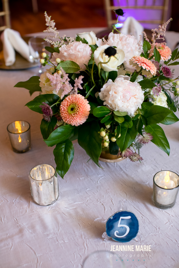 Wedding reception table centerpiece displays candles and flowers on a silver table linen and coral flowers
