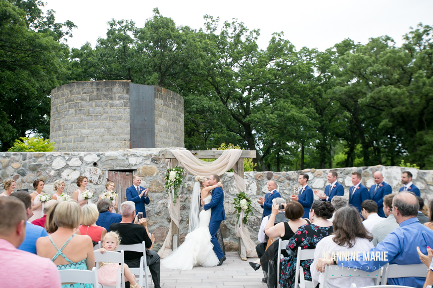 Ceremony kiss under the arch with wedding decorations and guests nearby