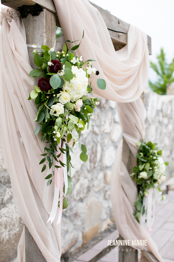 Taupe draping on a wedding ceremony arch with greenery and flowers