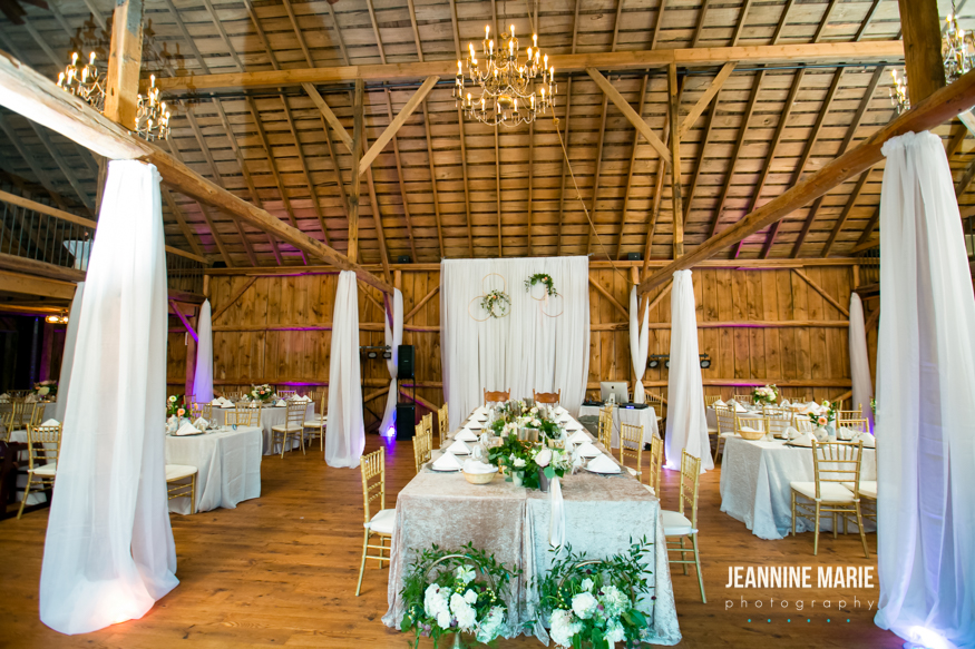 Reception draping on barn poles surrounding a head table with a velvet linen and greenery down the middle. Added to it is a backdrop for the husband and wife.