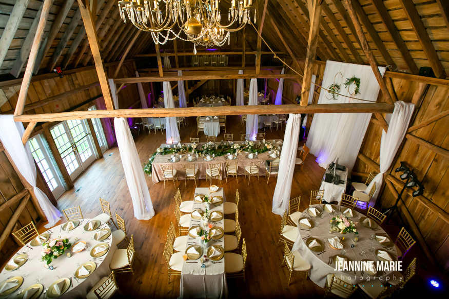 Overhead shot of wedding reception barn venue with linens, chiavari chairs, gold plates, champagne velvet, and candles
