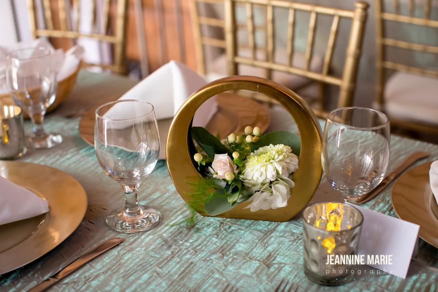 Shimmery table linen with gold accents and candles on guest tables at a wedding reception