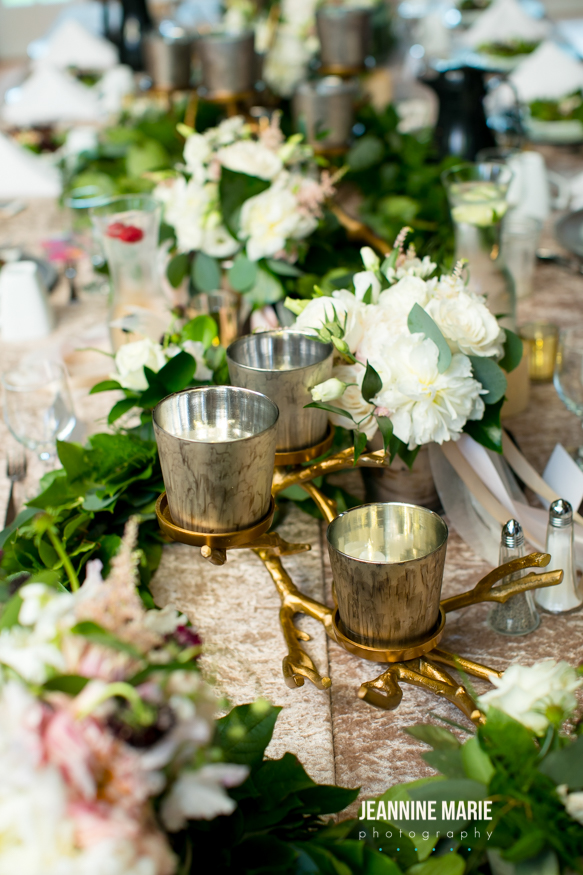upclose shot of white flowers, gold candle holder and candles with greenery and a champagne velvet table linen rental