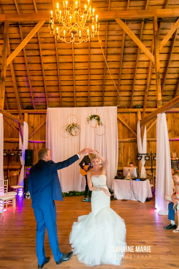 First dance at a wedding reception barn with a backdrop in place holding gold rings and greenery attached