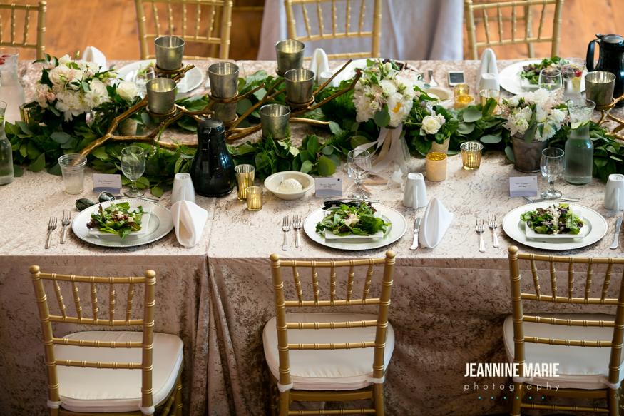 Head table display with lots of greenery and gold candle votives with silver plates and gold wedding decorations