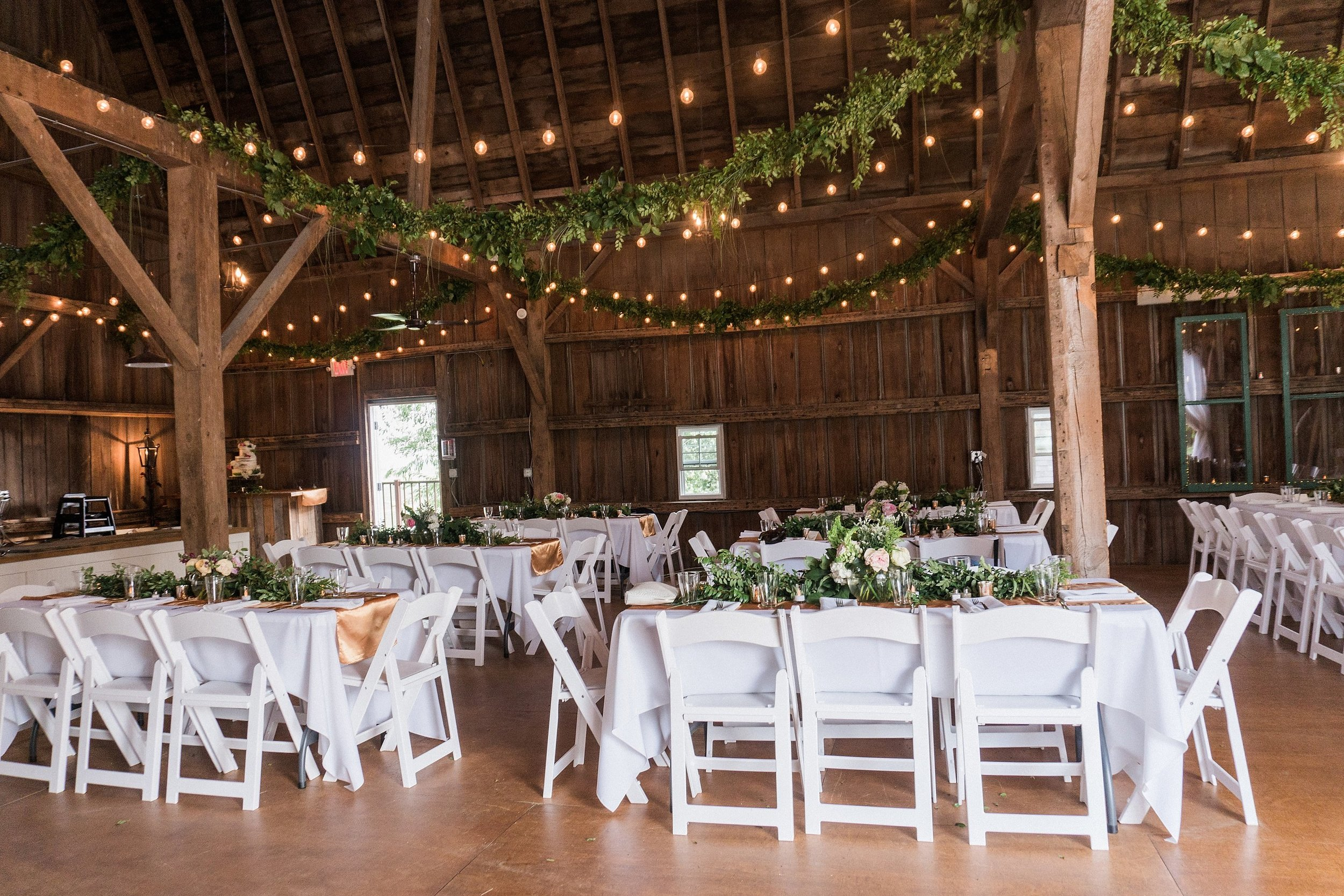 wedding reception inside a barn decorated with cafe lights and garland hanging from the ceiling and gold table runners on white table cloths