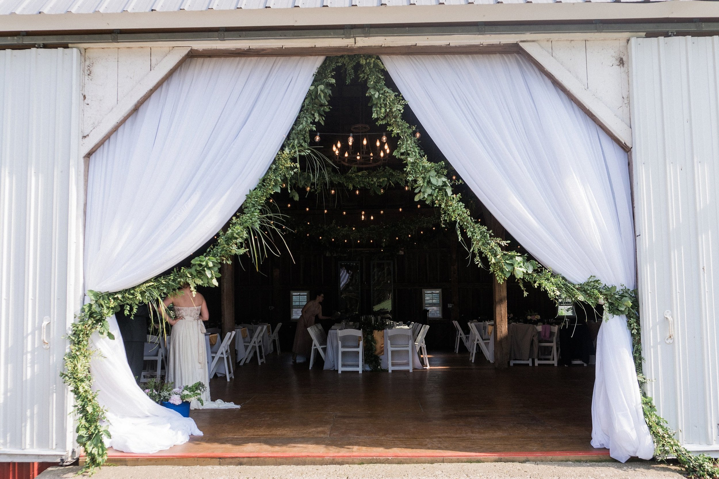 barn entrance draped with white curtains and garland