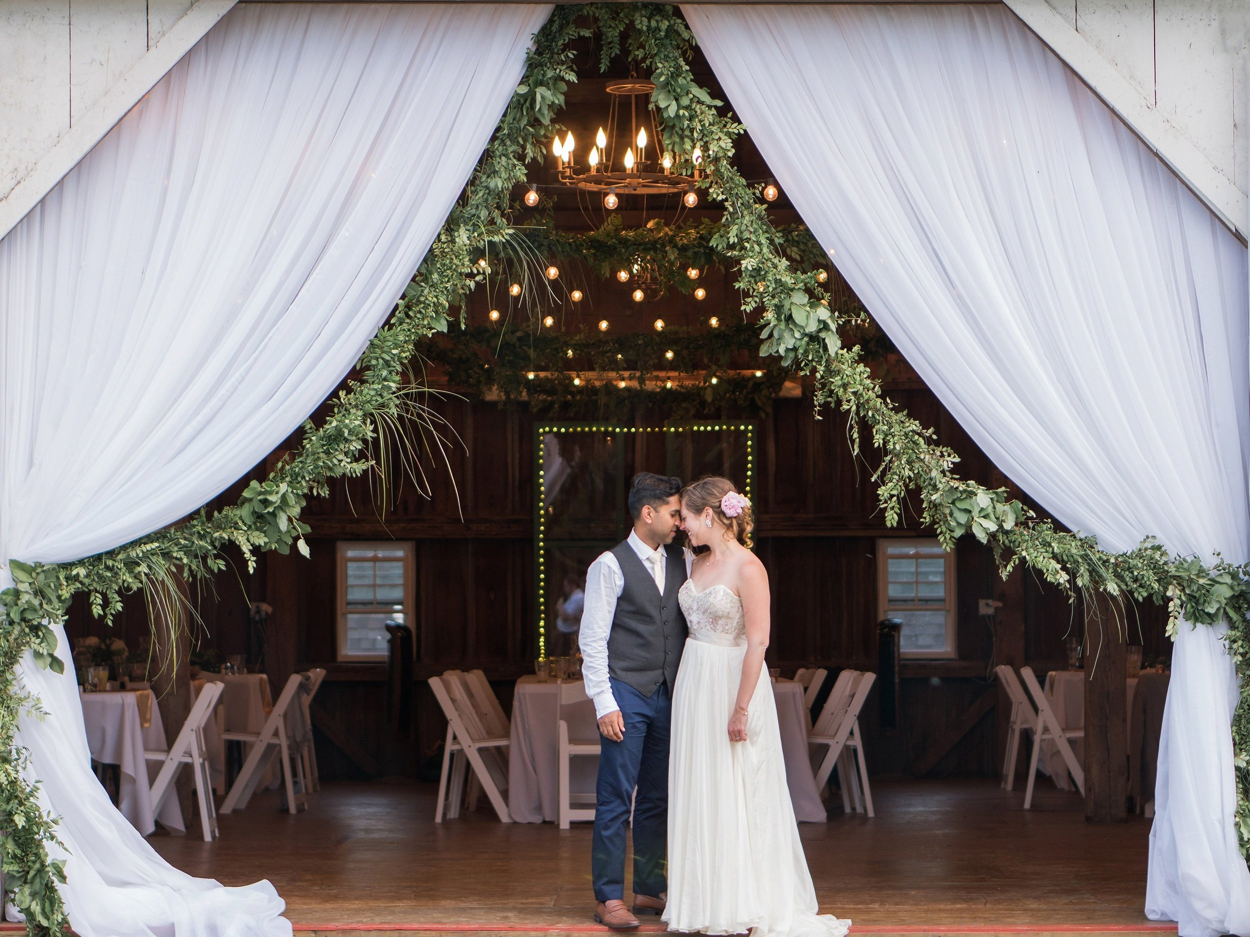 Newlywed couple in a barn entrance draped with white curtains pulled back with hanging greenery