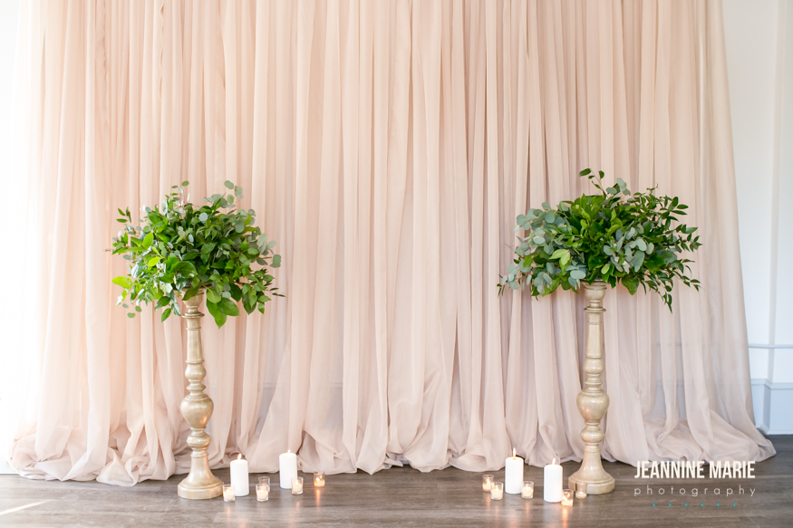 Taupe backdrop with champagne pedestals holding greenery arrangements complimented with glowing candles on the ground.