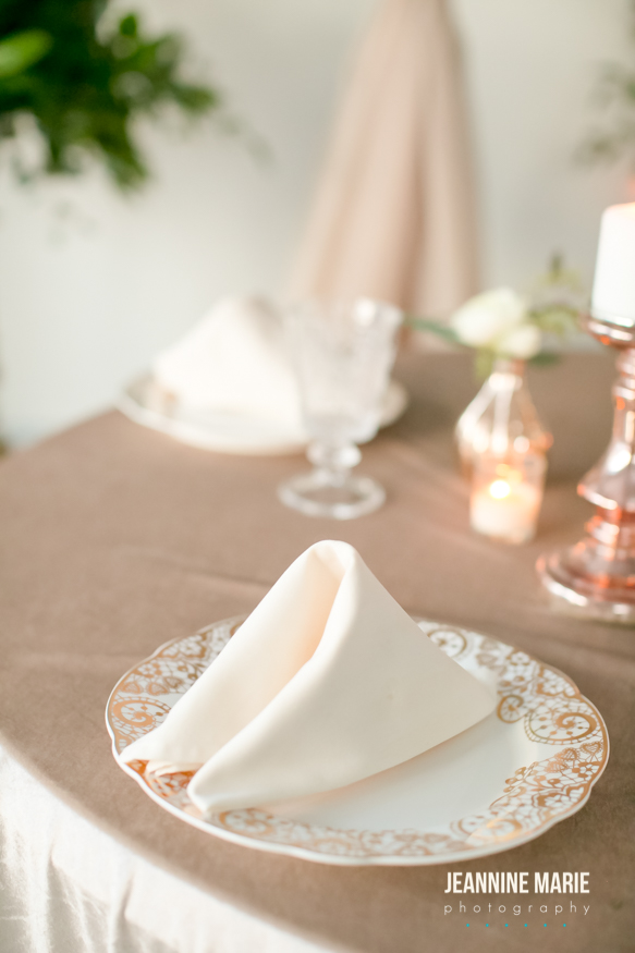 ivory napkin folded on a plate with neutral tone wedding decor