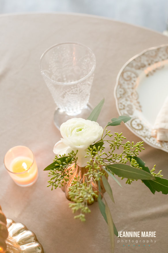 White flower in a mercury glass bud vase on a champagne linen with a candle nearby