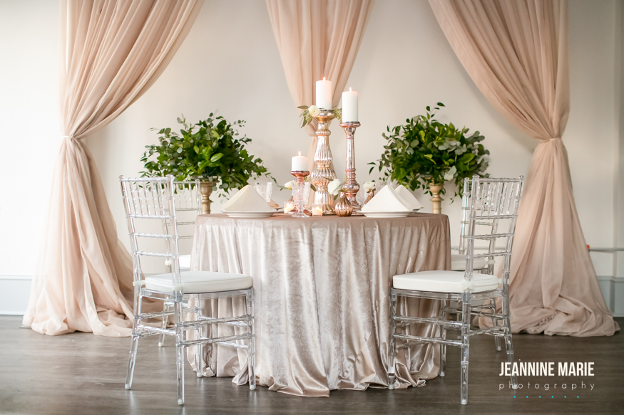 Wedding table set up with champagne table linen and surrounding chiavari chairs. For the centerpiece mercury glass candlesticks were used with flower bud vases and ivory napkins. Behind the table is a taupe backdrop and champagne pedestals holding greenery arrangements.