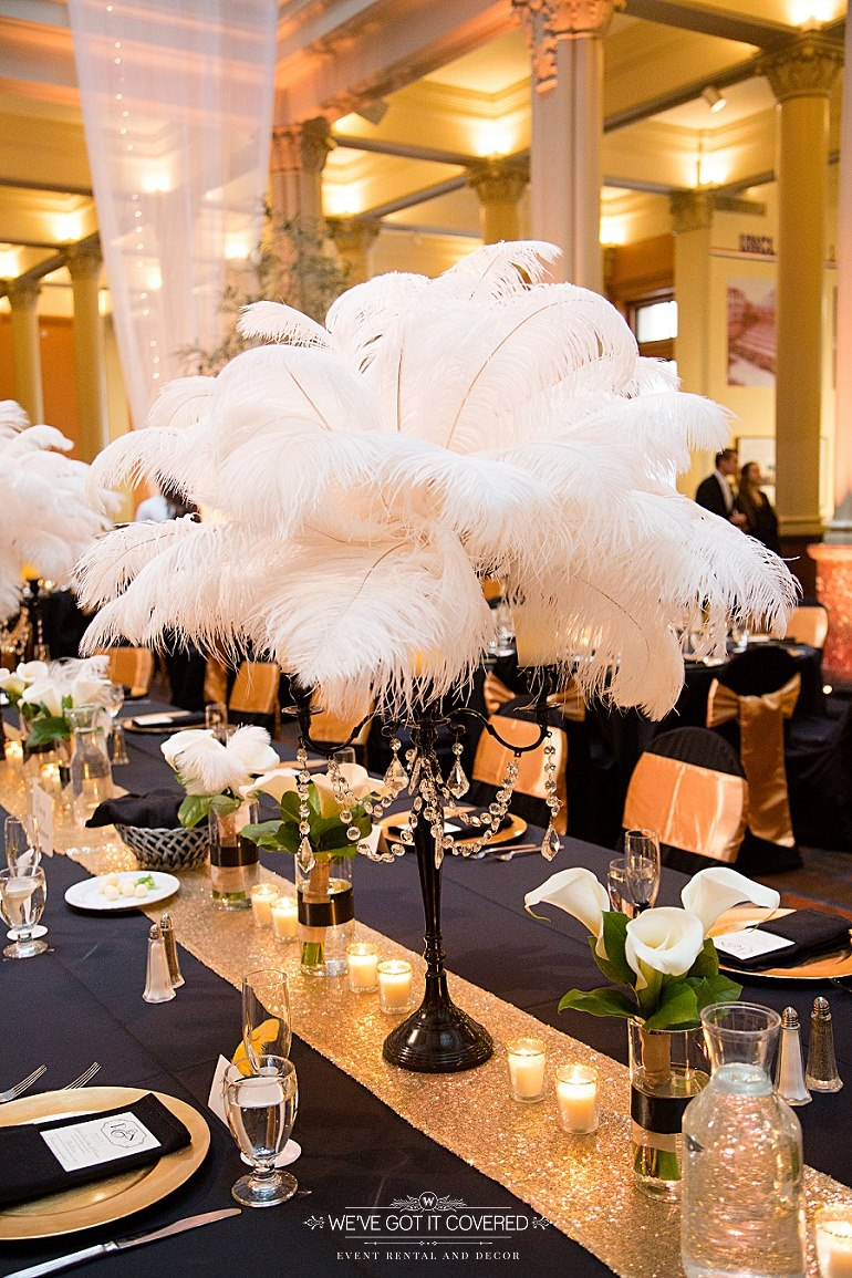 Focal centerpiece of a black candleabra holding white feathers. This was paired with a gold sequin runner and charger.