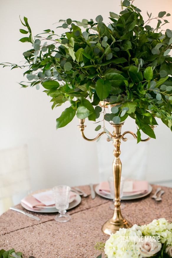 gold candleabra with voluptuous greens on a blush sequin linen