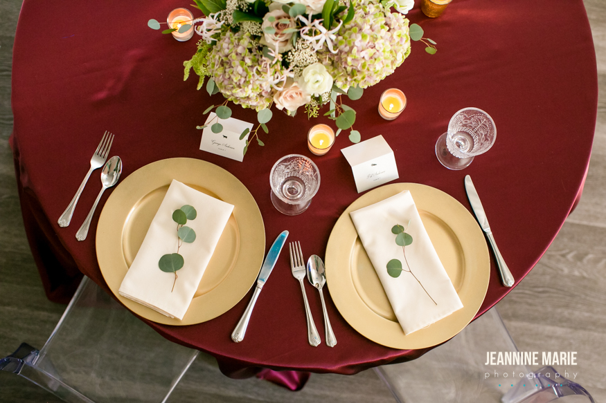 gold chargers and eucalyptus on a bold burgundy wedding linen with candles and flowers