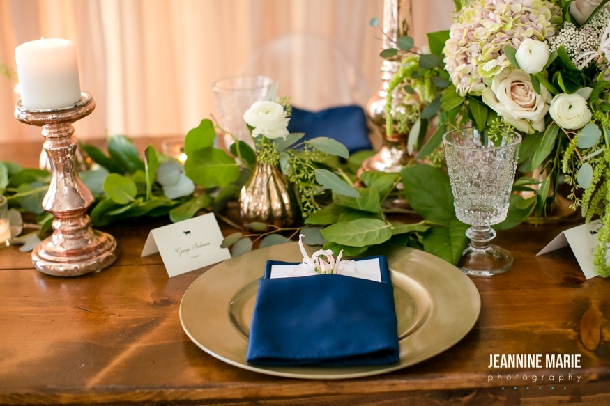 Gold charger and navy napkin on a farm table with eucalyptus