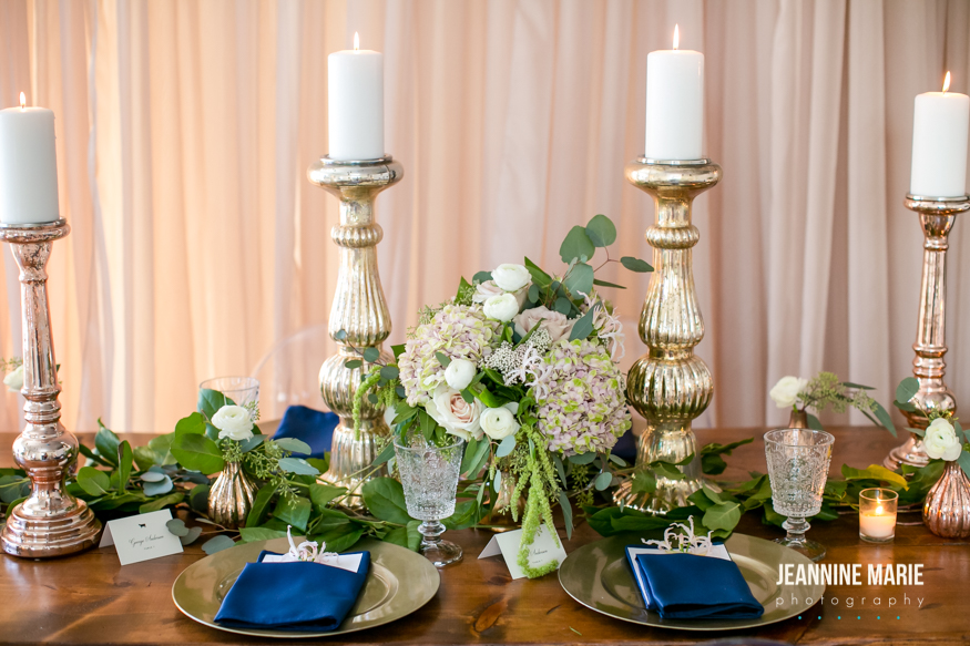 Four tall candlesticks on a farm table with greenery mixed in