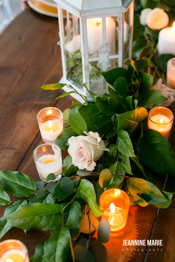 romantic candles intermixed with greenery and lantern decor