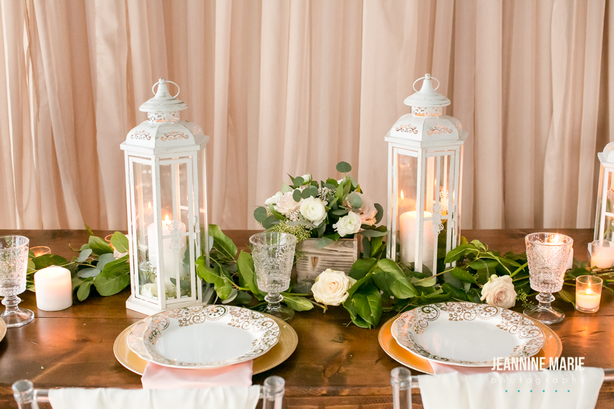 Long wood farm table with wedding decor of white lanterns, wood floral boxes, gold chargers and pink napkins