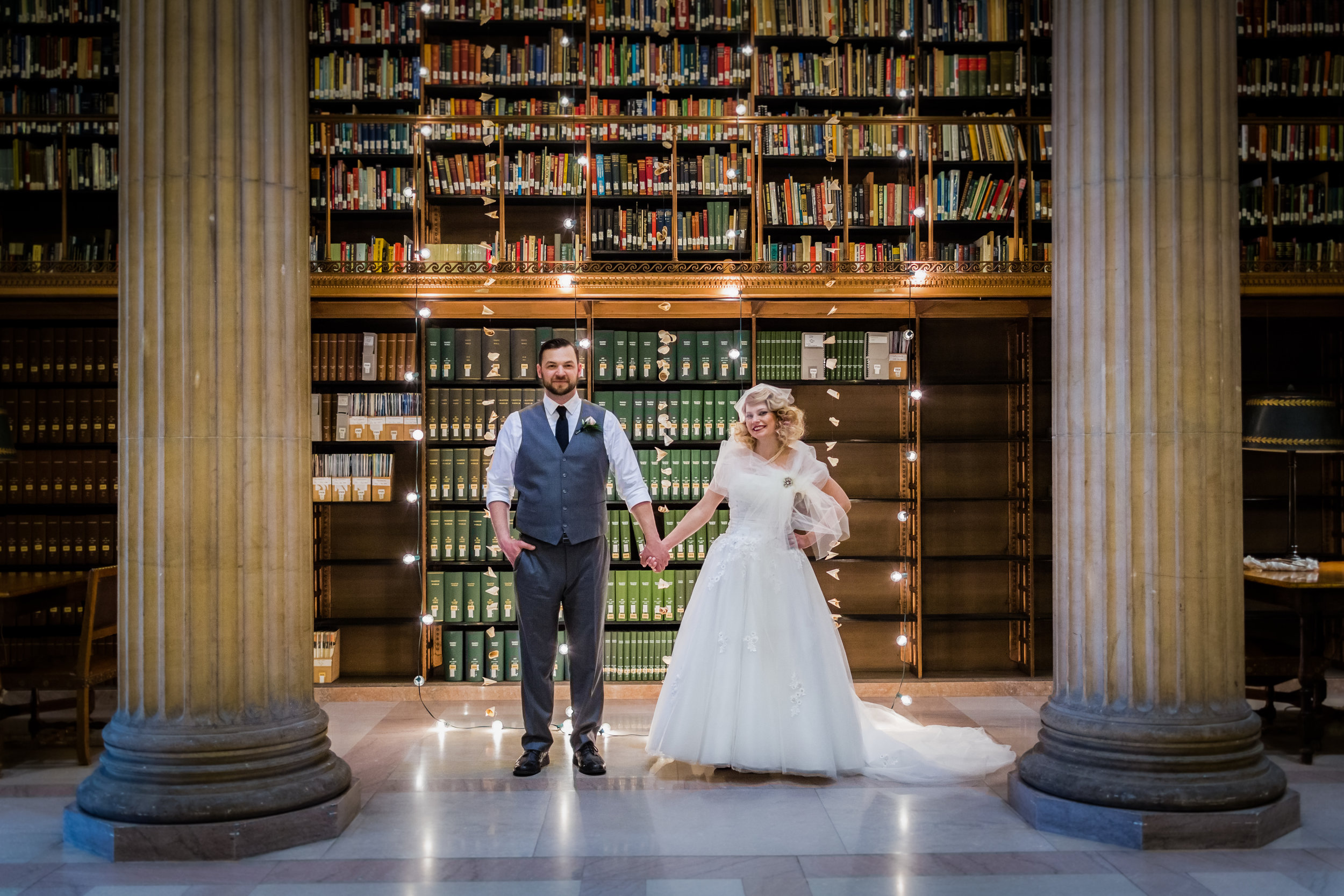 Married couple holding hands in front of cafe lighting waterfall and a bookshelf with books