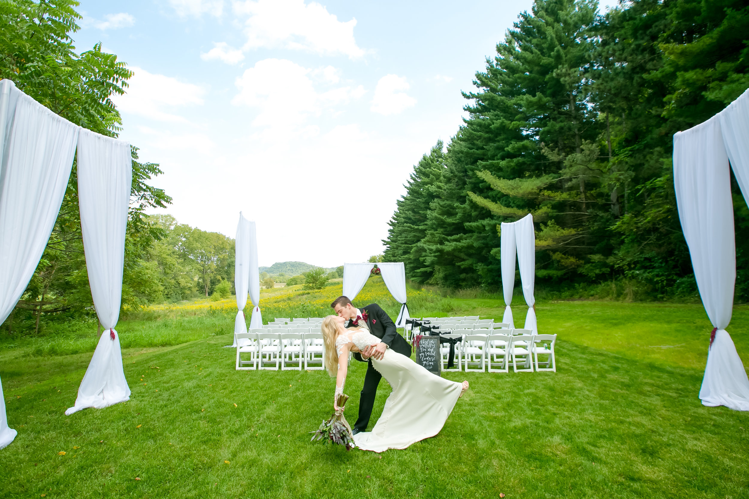 Outdoor ceremony site looking like a church with white curtains and chairs.