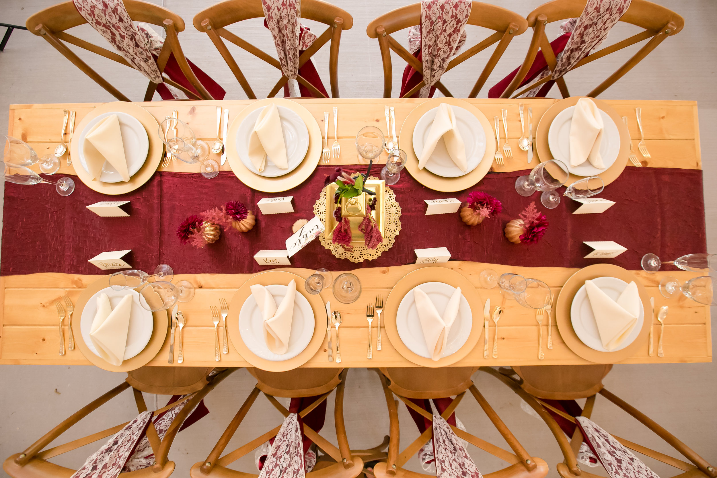 farmstyle tablescape with burgundy table runner and gold chargers