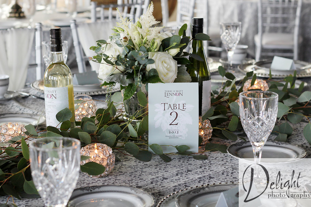 wedding reception inspiration with lace linens and table numbers displayed in front of white roses