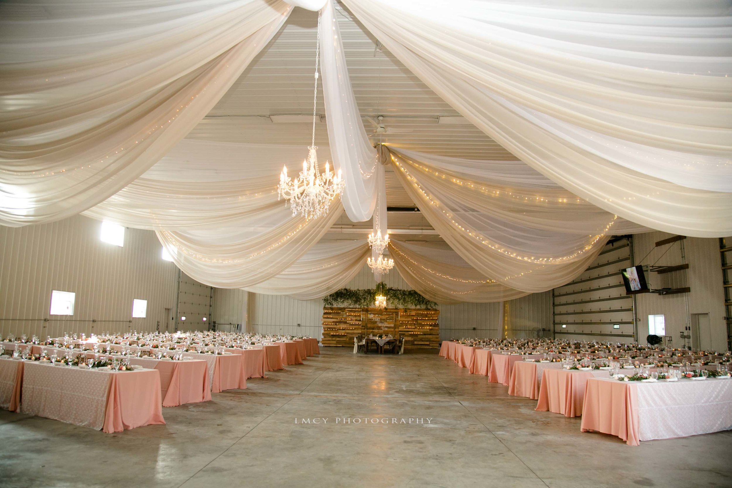 Warehouse reception set up with draping and chandeliers with pink tables and lace overlays