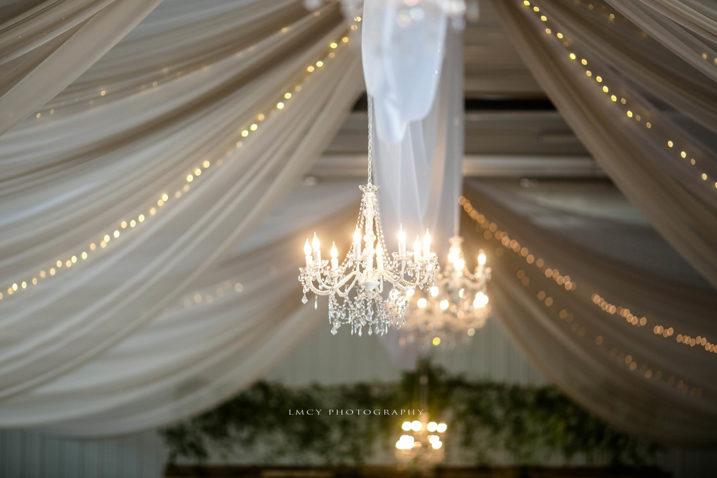 taupe and white draping with twinkle lights and chandeliers