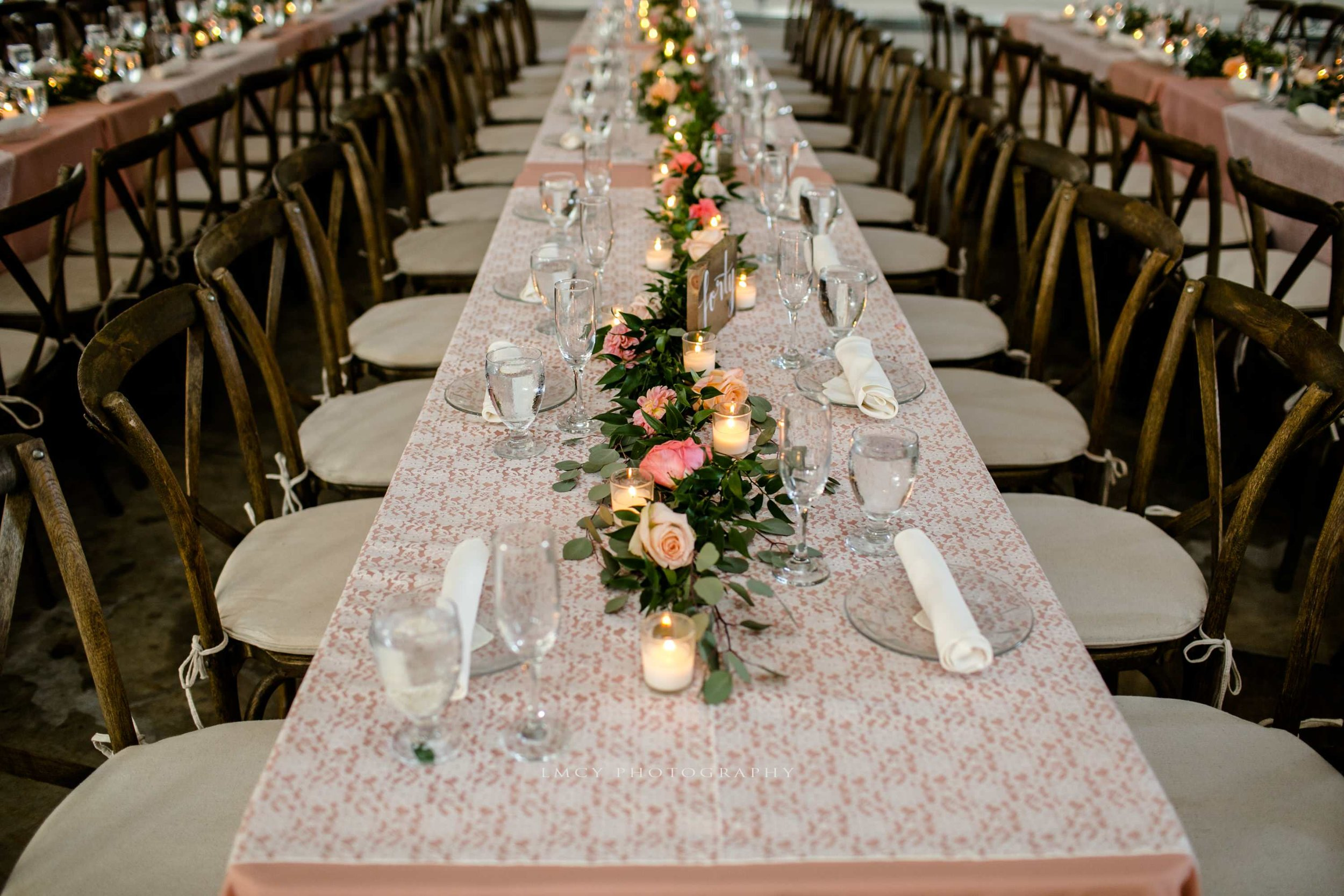 pink table linens with lace overlays and green garland centerpieces