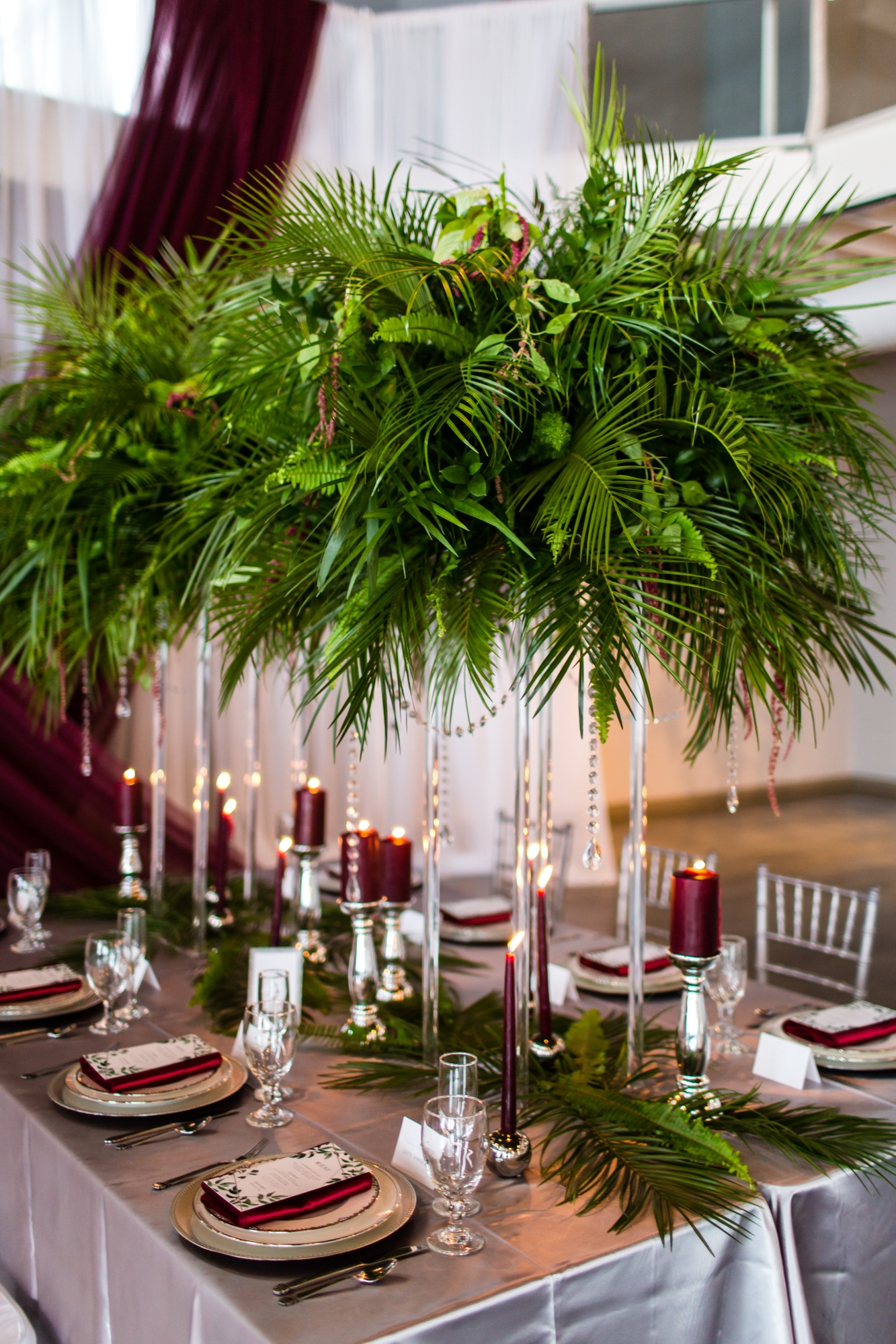 silver satin table linens with fern greenery and burgundy candles