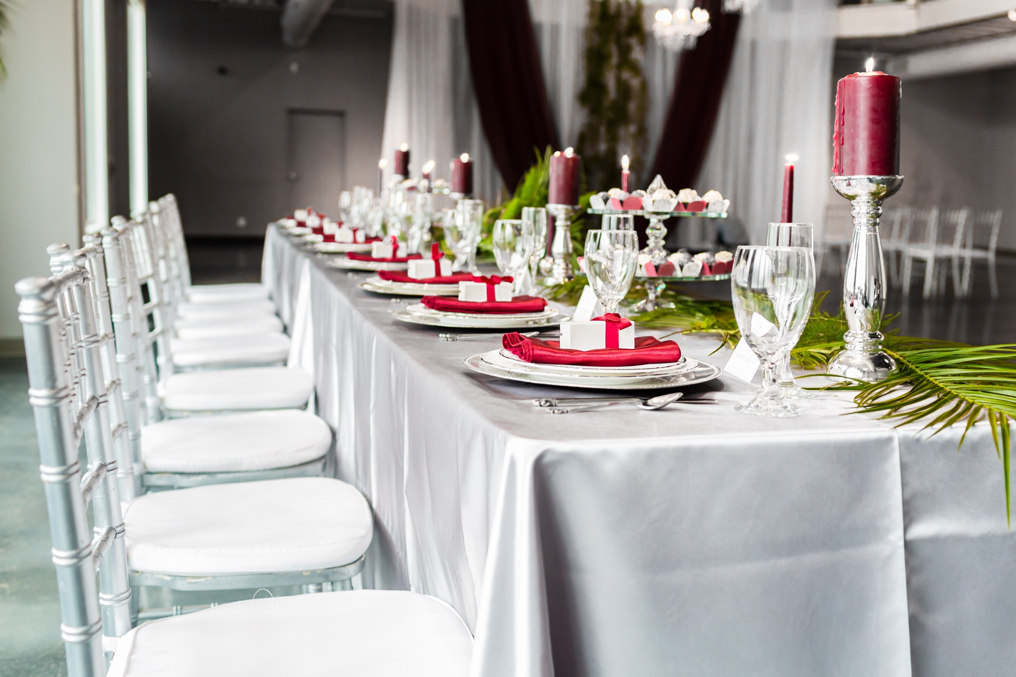 Head table set up with burgundy accents and fern greenery